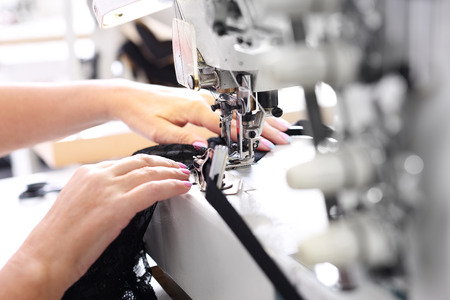fashion design: Sewing on a machine. Seamstress sewing on the sewing machine in the manufacturing plant