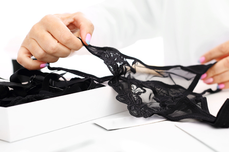 feminine hands: Sensual lingerie, beautiful gift for a woman.Hands women packing lacy underwear in a box
