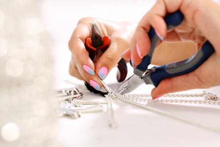 Workshop sieraden. Vrouwelijke hand voert juwelen