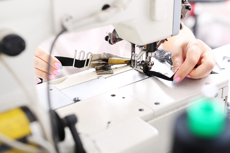 stitching machine: Seamstress sewing on the sewing machine in the manufacturing plant