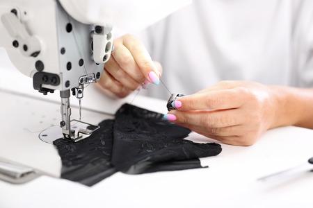 stitching machine: Sewing on a machine. Seamstress sewing on the sewing machine in the manufacturing plant