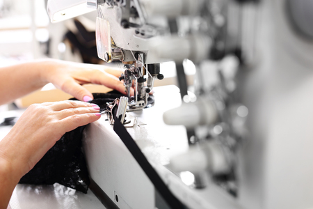 Sewing machine. Seamstress sewing on the sewing machine in the manufacturing plant 스톡 콘텐츠
