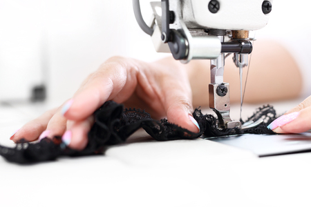 Sewing machine. Seamstress sewing on the sewing machine in the manufacturing plant Stock Photo