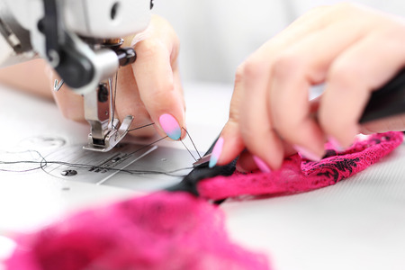 seamstress: Seamstress. Seamstress sewing on the sewing machine in the manufacturing plant Stock Photo