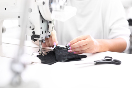 Seamstress. Seamstress sewing on the sewing machine in the manufacturing plant Stock Photo