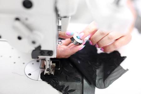 presser: Seamstress. Seamstress sewing on the sewing machine in the manufacturing plant Stock Photo