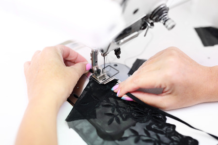 presser: Sewing on a machine. Seamstress sewing on the sewing machine in the manufacturing plant