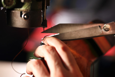suede belt: Sewing machine. shoemaker sews shoes Stock Photo
