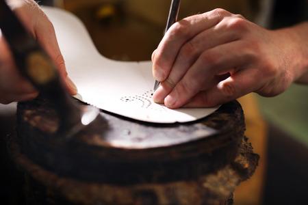 suede belt: Shoemaker. Cobbler shoemaker sews elegant shoes