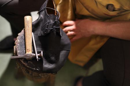 shoes: Shoemaker. Cobbler shoemaker sews elegant shoes