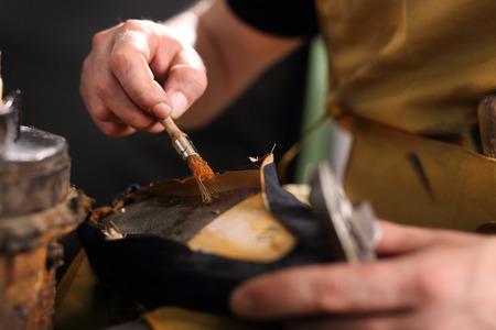 suede belt: Bonding shoes. Shoemaker. Cobbler shoemaker sews elegant shoes