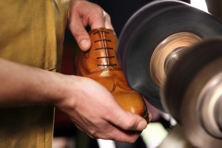 Polishing shoes. Polisher cobbler polishes on brown shoes