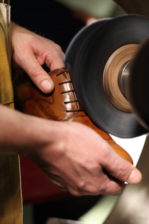Shoemaker. Grinding shoes in shoe manufacturing plant