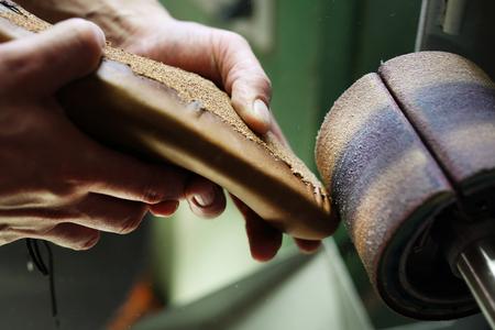 suede belt: Shoemaker. Grinding shoes in shoe manufacturing plant