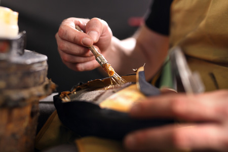 Shoe repair. shoemaker performs shoes in the studio craft