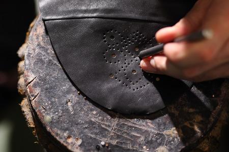 suede belt: Punch leather for shoes. Shoemakers workshop, append Grinding cast heels shoes in shoe manufacturing plant Work shoemaker, an artist craftsman Punch leather for shoes shoemaker.