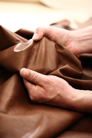 Die Anlage Lederhandwerker. Hände maßgeschneiderte, um die Qualität des Materials zu überprüfen Standard-Bild - 45679055