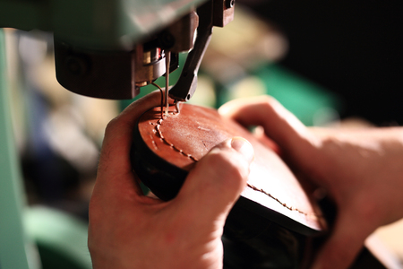 Shoemaker sews shoes. Shoemaker manually performs shoes in the studio craft