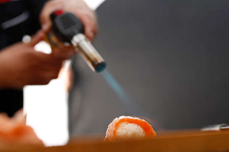 tans: Sushi with raw salmon burning flame Stock Photo