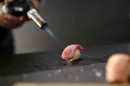 sushi: Portion of rice formed into a ball covered with a piece of fish Stock Photo