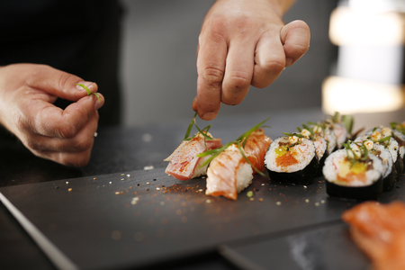 sushi restaurant: Sushi Master prepares futomaki Stock Photo