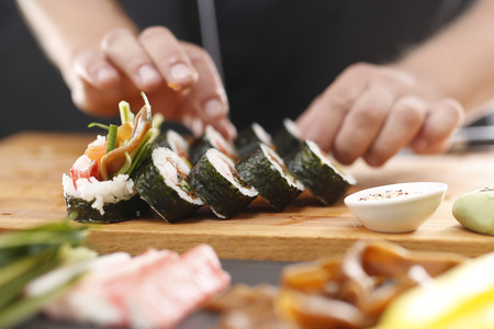 replaces: Sushi stages of preparing sushi with salmon, crab finger, cucumber gourd wrapped in nori algae
