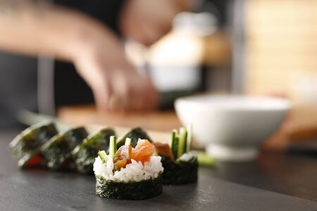 cooking ingredients: Slicing sushi with crab, salmon, cucumber