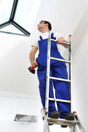 roof windows: A man dressed working working at the installation of roof windows