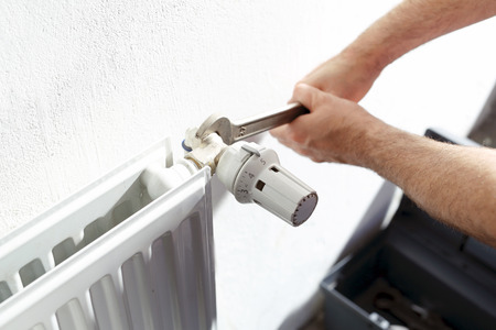 fontanero: Fontanero aprieta la válvula en la llave hidráulica calentador