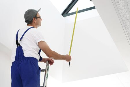 lighting technician: Measurement and man in overalls with a measuring tape standing on a ladder