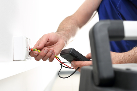 wireman: Electrician. Man mounts in a wall electrical outlet, Internet connection Stock Photo
