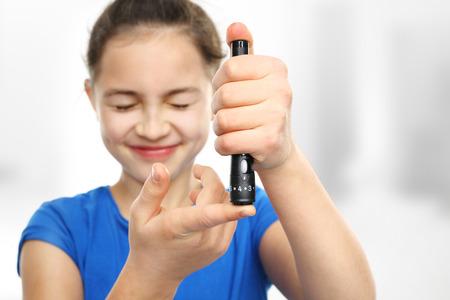 metro de medir: Chica con la diabetes es una medida de los niveles de azúcar en la sangre utilizando un glucómetro