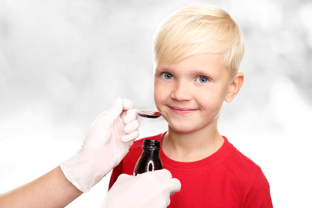 cold cure: A delicious syrup, the boy drink a cure for the common cold.