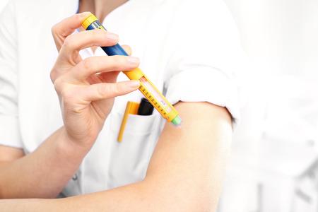 inyeccion: Una mujer inyecta la insulina en el brazo Foto de archivo