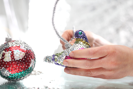 balls decorated: Woman performs Christmas tree ornaments. Styrofoam balls decorated with colorful sequins