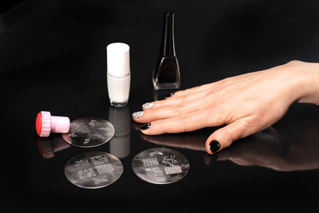 manicura: Sellos Se aplica la laca de uñas esteticista en placa Foto de archivo