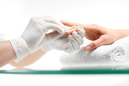 cotton ball: Removal of nail varnish. manicure. Beautician Removes nail polish with a cotton ball soaked in acetone. Stock Photo