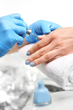 manicure: Beautician painting nails. Colored manicure, cosmetic colored lacquer painting nails Stock Photo