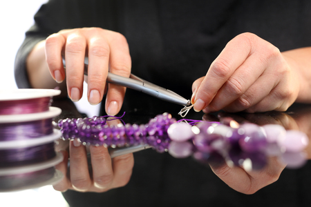 threading: Necklace, amethyst fuchsia. Threading beads, jewelry workshop Stock Photo