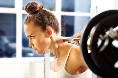 warm up: Weight lifting. The woman is picking barbell in gym