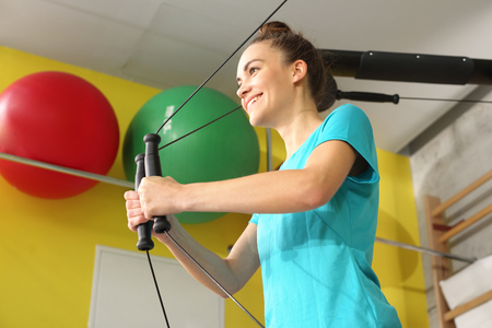muscle woman: Rehabilitation, training with rubbers. Stock Photo