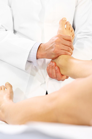 physical test: The doctor orthopedist, physical therapist examines the patients leg