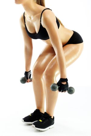 sports attire: dumbbells. Woman in sports attire raises the weights.
