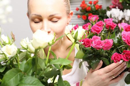 mujer con rosas: Oler las rosas, la mujer que huele un ramo de hermosas rosas Foto de archivo