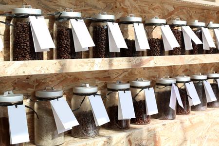 Koffiebrander. Plank met potten van koffiebonen