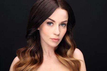 Portrait d'une belle femme aux cheveux longs sur un fond noir Banque d'images