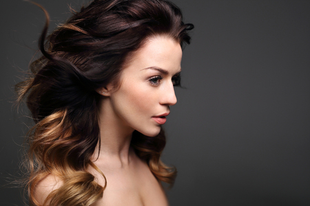 Curls, hair full of volume. Portrait of a beautiful woman on a black background.
