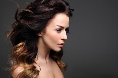 Curls, Haar voller Volumen. Porträt einer schönen Frau auf einem schwarzen Hintergrund.