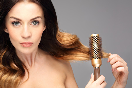 modeling: Laying, modeling hair on a round brush.