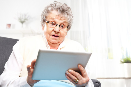 age old: Surprised elderly woman looks in the tablet screen